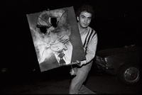 A young man displays a defaced portrait of the Shah.
