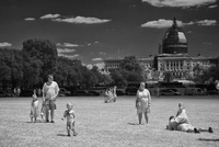 A tourist family on the Mall in front of the Air & Space Museum, the Capitol in the distance