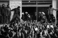 Ayatollah Khomeini salutes the crowds from his small school room office.
